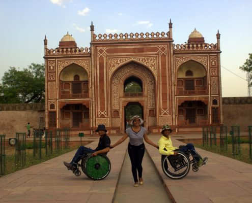 two people on wheelchair with a volunteer in Agra