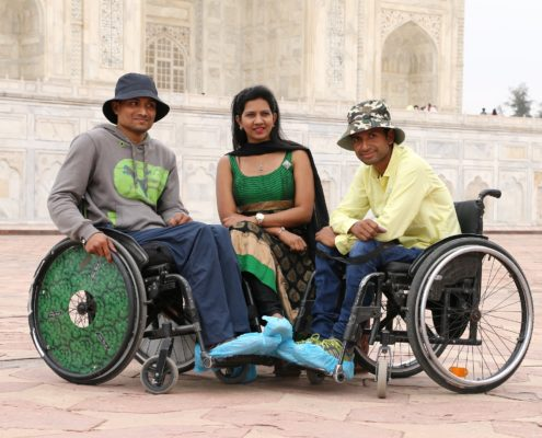 A volunteer with two disabled people at Taj Mahal