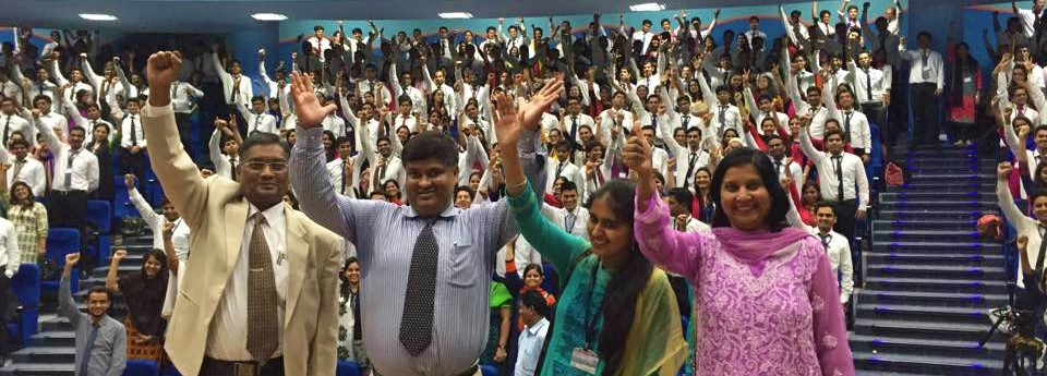 Asif waving for a photograph after delivering a lecture with students in the background.