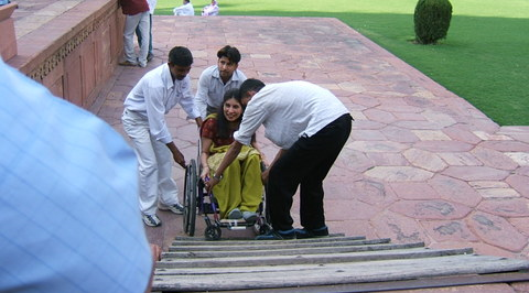 Sunita being helped by three men to take the ramp to the monument