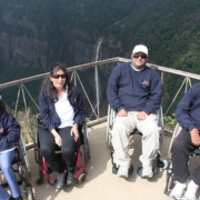 The team of four poses on a balcony with hills and waterfalls behind their back