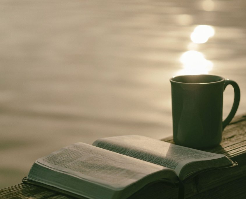An open book and cup of coffee in the fading evening sun with a backdrop of still water with the sun's reflection