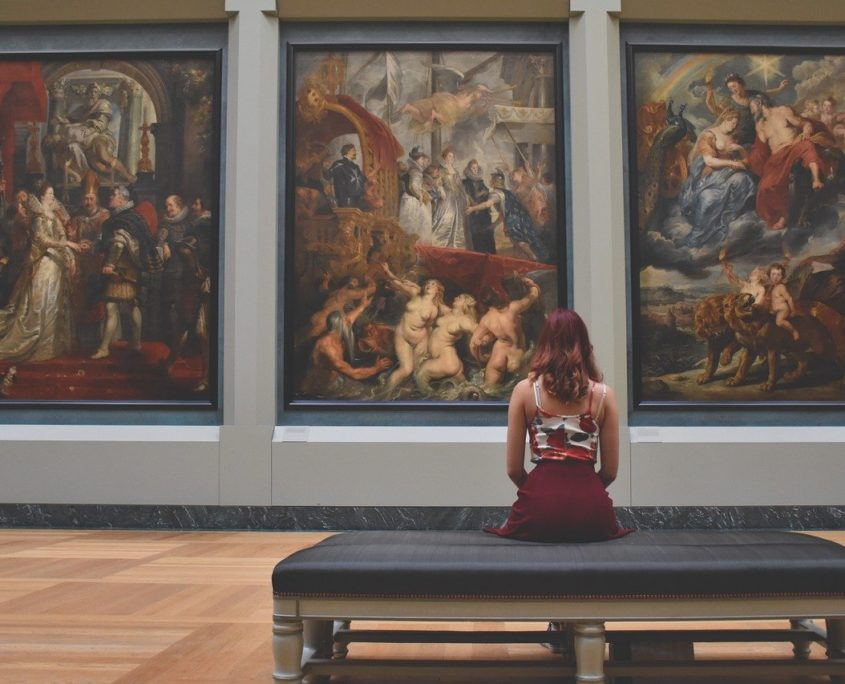The back of a lady seated and looking at the large paintings in front of her at an art gallery